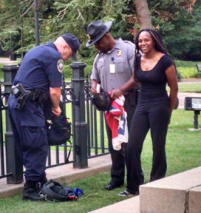 Bree Newsome getting arrested after scaling pole and removing flag - Credit: NecolBitchie.com