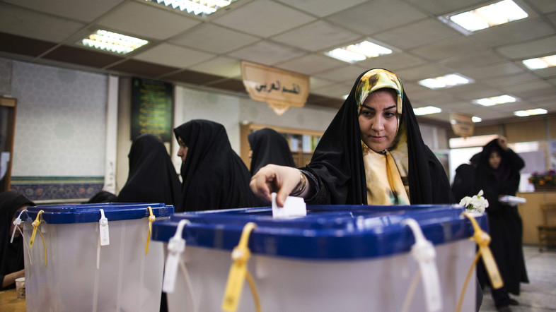 An Iranian woman casts her ballot to vote for both parliamentary elections and Assembly of Experts at a polling station at Massoumeh shrine in the holy city of Qom, 130 kms south of Tehran, on February 26, 2016. Iranians will vote for both parliamentary elections and the Assembly of Experts in an elections billed by the moderate president as vital to curbing conservative dominance in parliament and speeding up domestic reforms after a nuclear deal with world powers. / AFP / BEHROUZ MEHRI
