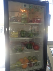 Refrigerated case with fresh fruit and vegetables.